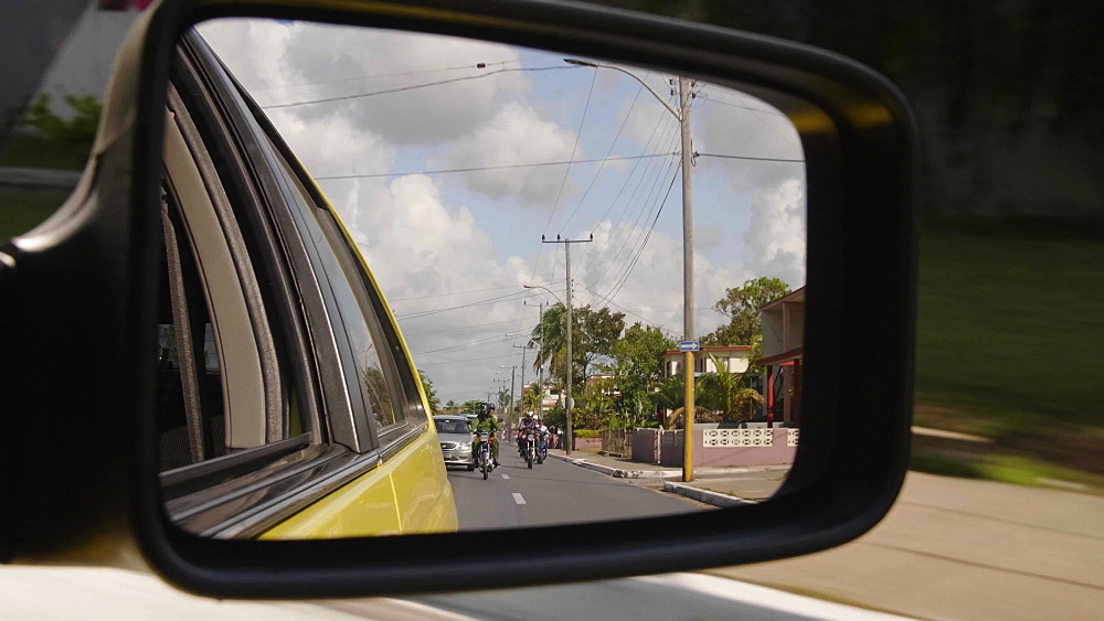 View of cars and motocycles in the side mirror of the taxi car in Matanzas, Cuba, West Indies, Caribbean, Central America