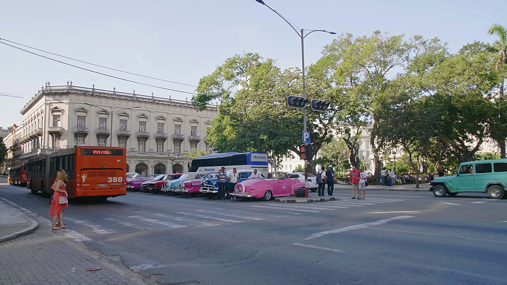 Tourists crossing road and colourful old American taxi cars parked in Havana, La Habana, Cuba, West Indies, Caribbean, Central America