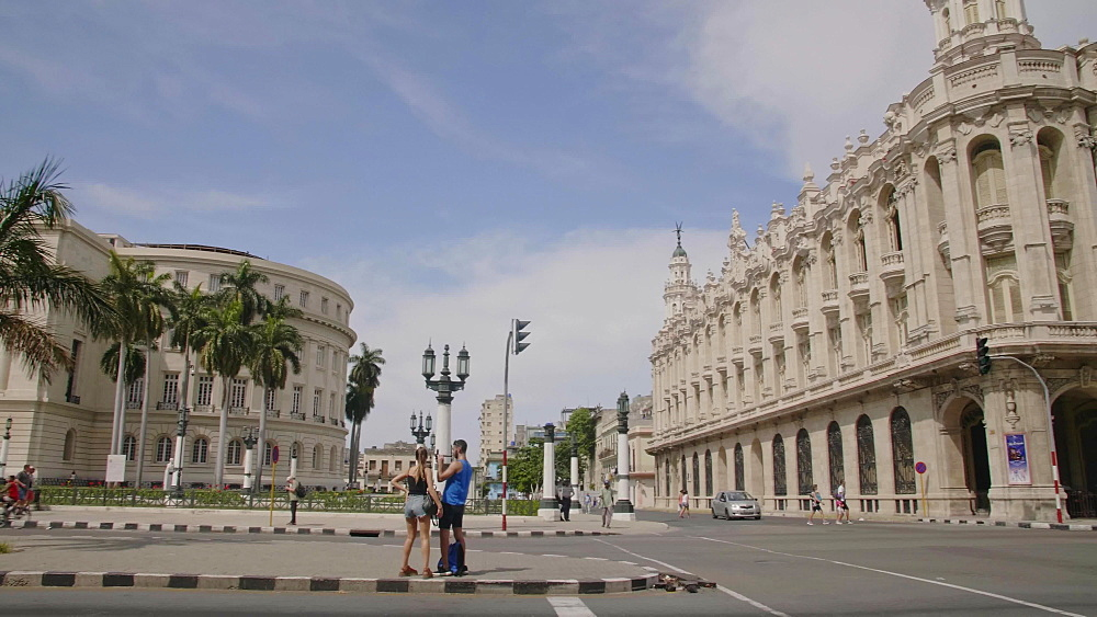 Old American cars drive past the Gran Teatro de La Habana and El Capitolio in Havana, Cuba, West Indies, Caribbean, Central America