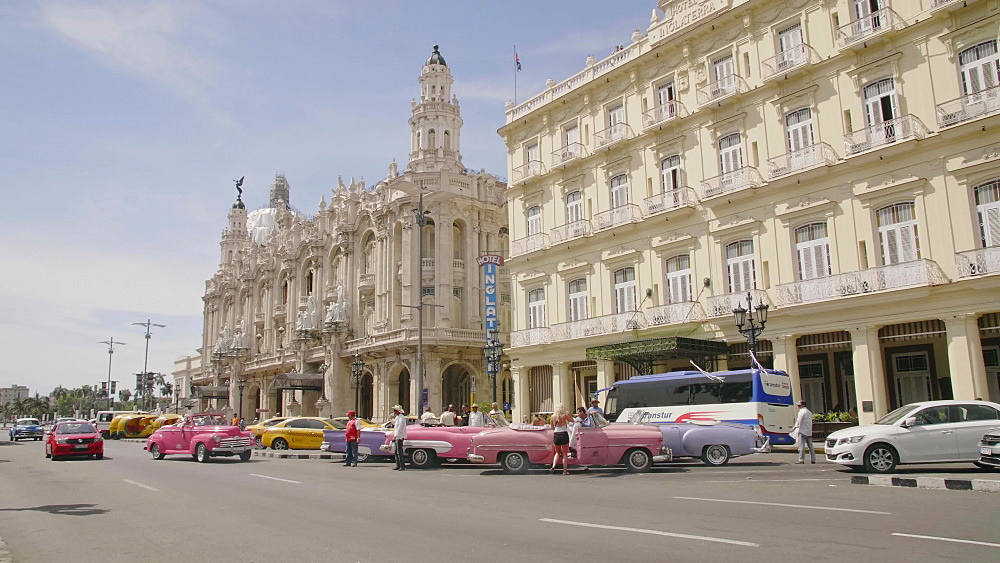 Old American cars drive past the Gran Teatro de La Habana in La Habana (Havana), Cuba, West Indies, Caribbean, Central America