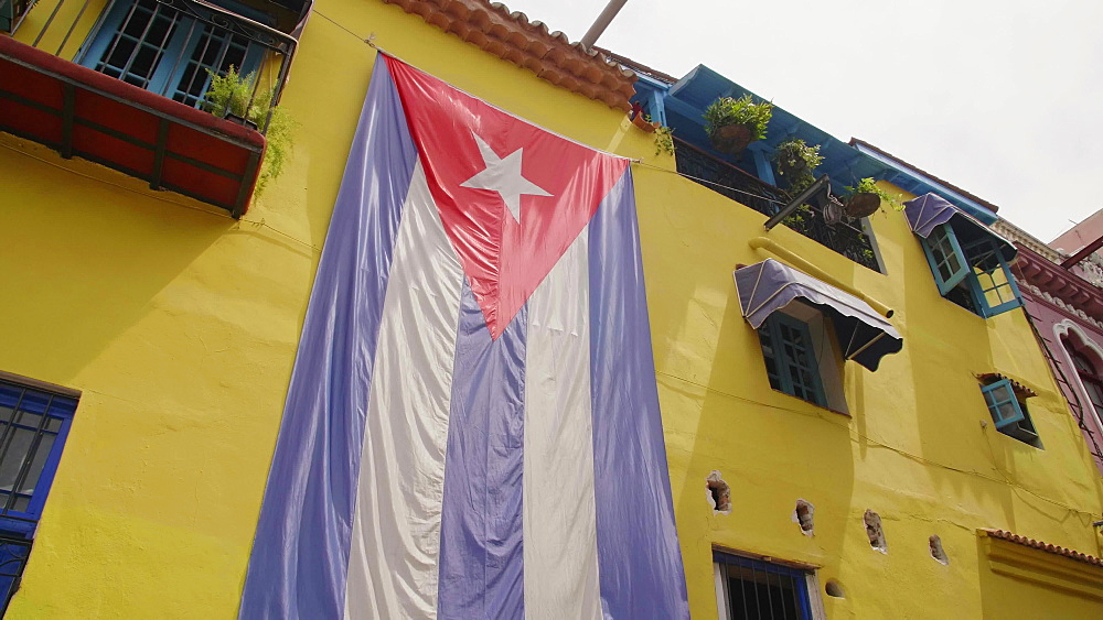 Huge Cuban flag on yellow building in Havana, La Habana (Havana), Cuba, West Indies, Caribbean, Central America