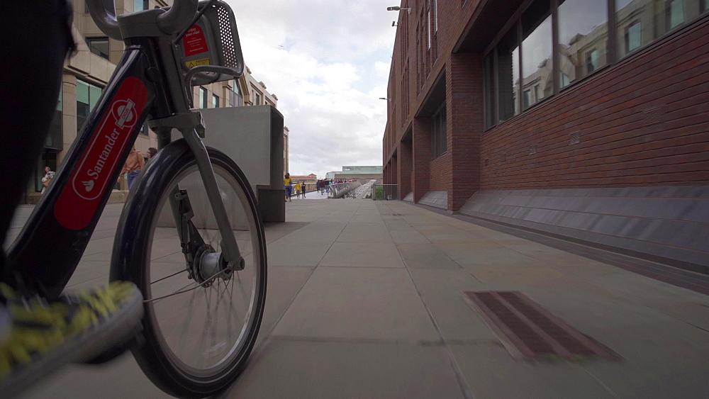 Santander city bike riding through Peter's Hill, Southwark, London, England, United Kingdom, Europe