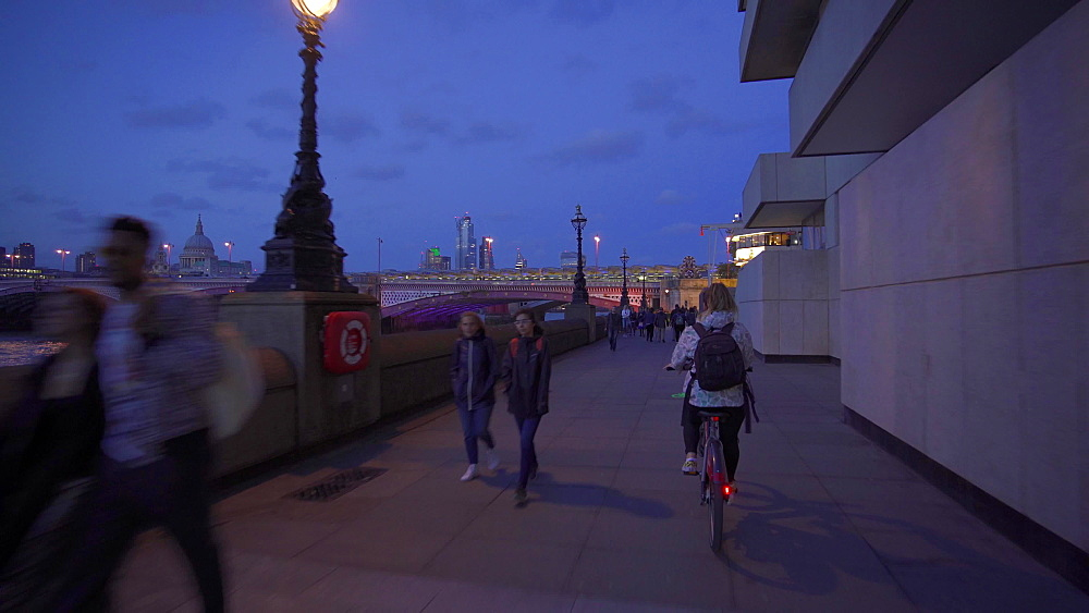 Santander city bike riding along London Riverside, Blackfriars Railway Bridge, Thames River and St. Pauls Cathedral at night, London, England, United Kingdom, Europe
