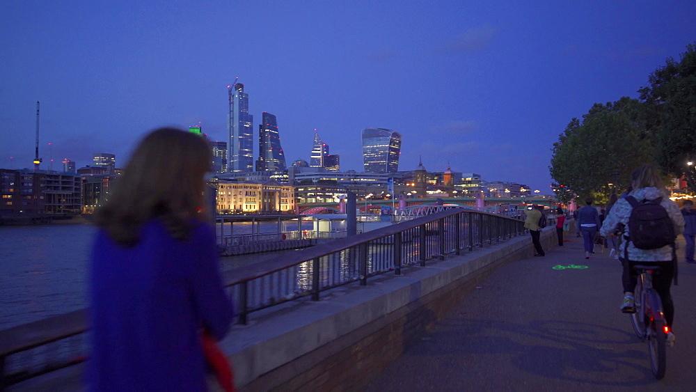 Tracking shot along London Riverside, Blackfriars Railway Bridge, Thames River and St. Pauls Cathedral at night, London, England, United Kingdom, Europe