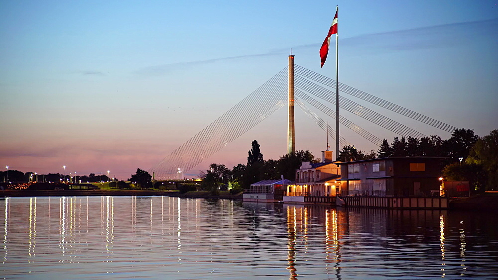 Suspension bridge with huge Latvian flag from AB dam at sunset, Riga, Latvia, Europe