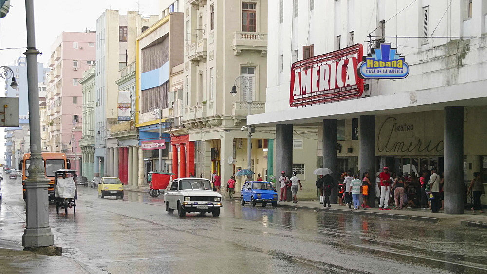 Old vintage cars and rickshaw in the rain nest to Teatro America, La Habana (Havana), Cuba, West Indies, Caribbean, Central America