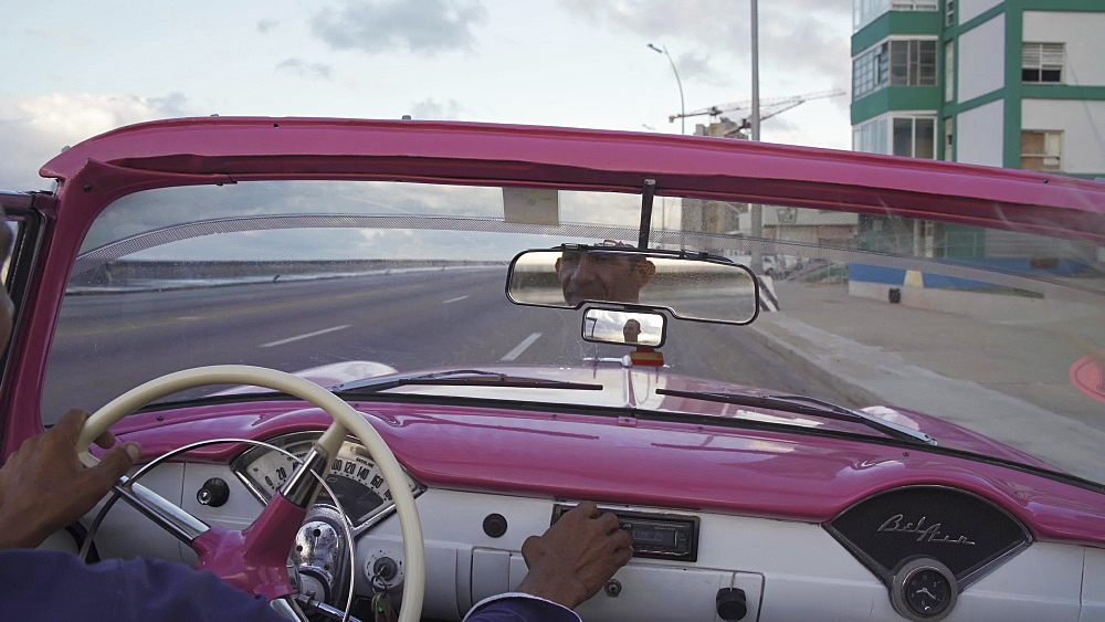 Local classic car driver driving on The Malecon at sunset, Havana, Cuba, West Indies, Caribbean, Central America