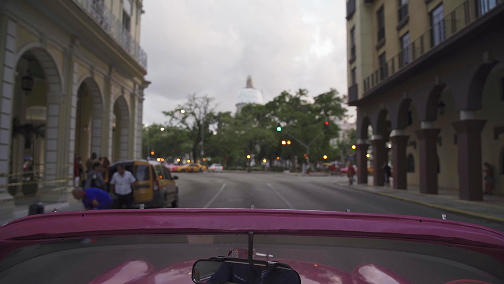 Local classic car driver showing Havana at dusk, Cuba, West Indies, Caribbean, Central America