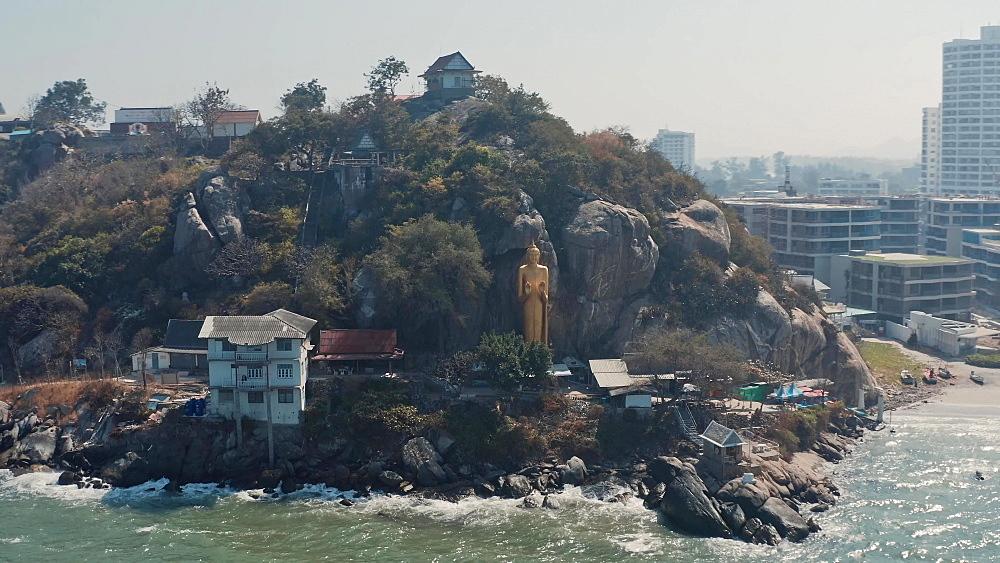 Drone Aerial shot of a huge gold Buddha statue at Hua Hin beach, Prachuap Khiri Khan Province, Thailand