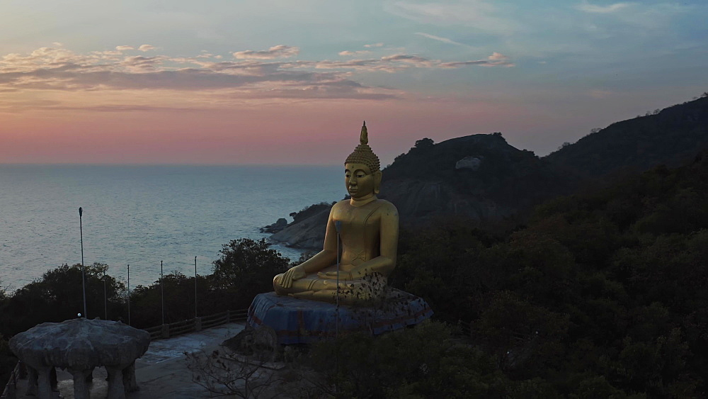 Drone aerial shot of a huge gold Buddha statue at sunset, Hua Hin beach, Prachuap Khiri Khan Province, Thailand, Southeast Asia, Asia
