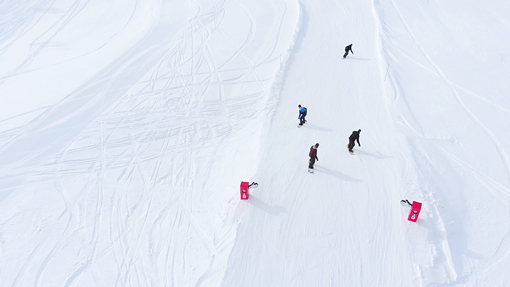 Aerial drone shot of snowboarders going down the slope La Plagne ski resort, Tarentaise, Savoy, French Alps, France, Europe