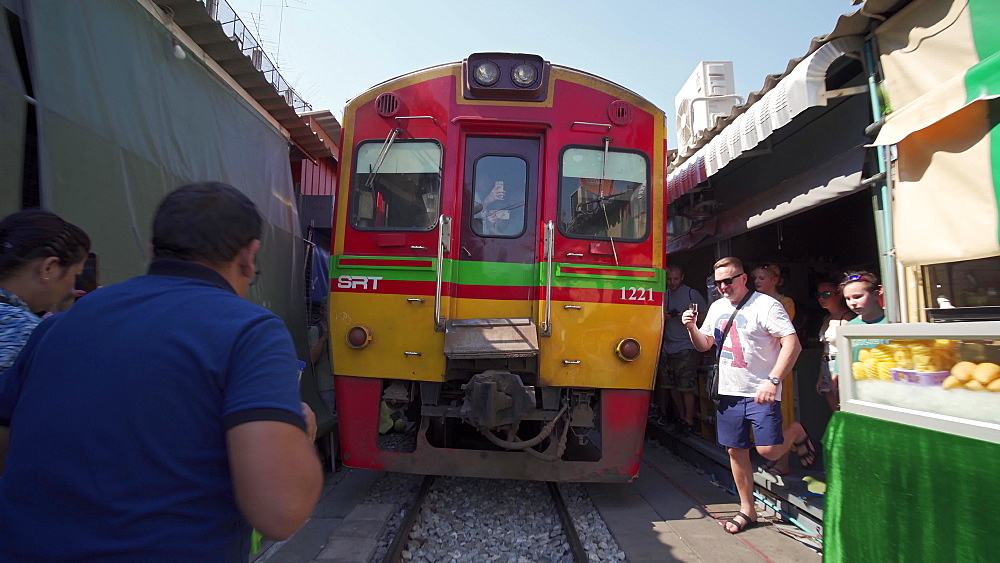 Gimbal video of Train going through Maeklong Railway Market, Bangkok, Thailand, Southeast Asia, Asia