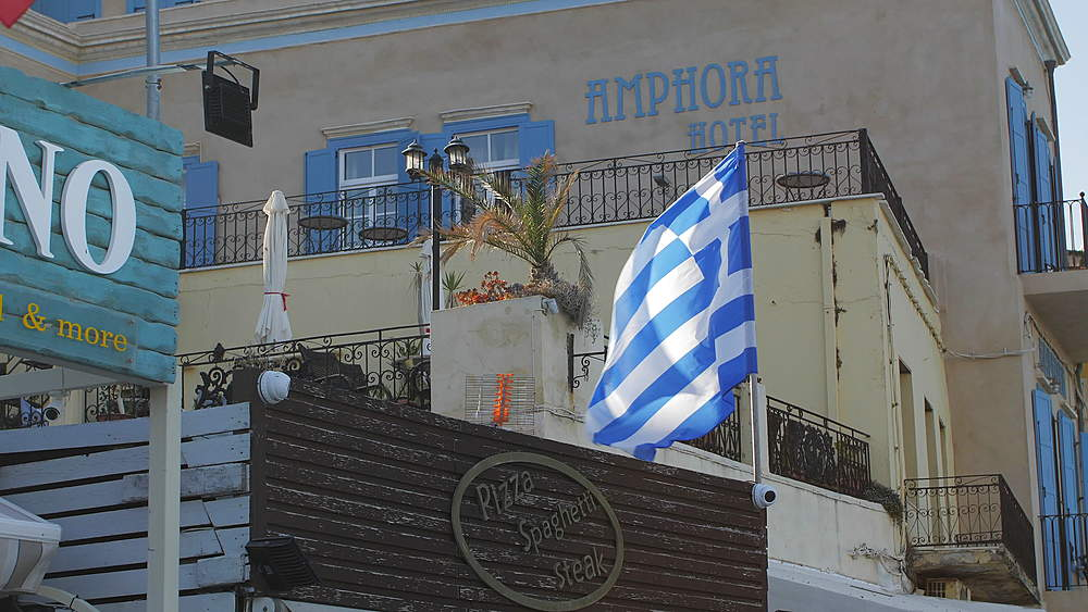 The Venetian era harbour and Greek flag at the Mediterranean port of Chania, Crete, Greek Islands, Greece, Europe