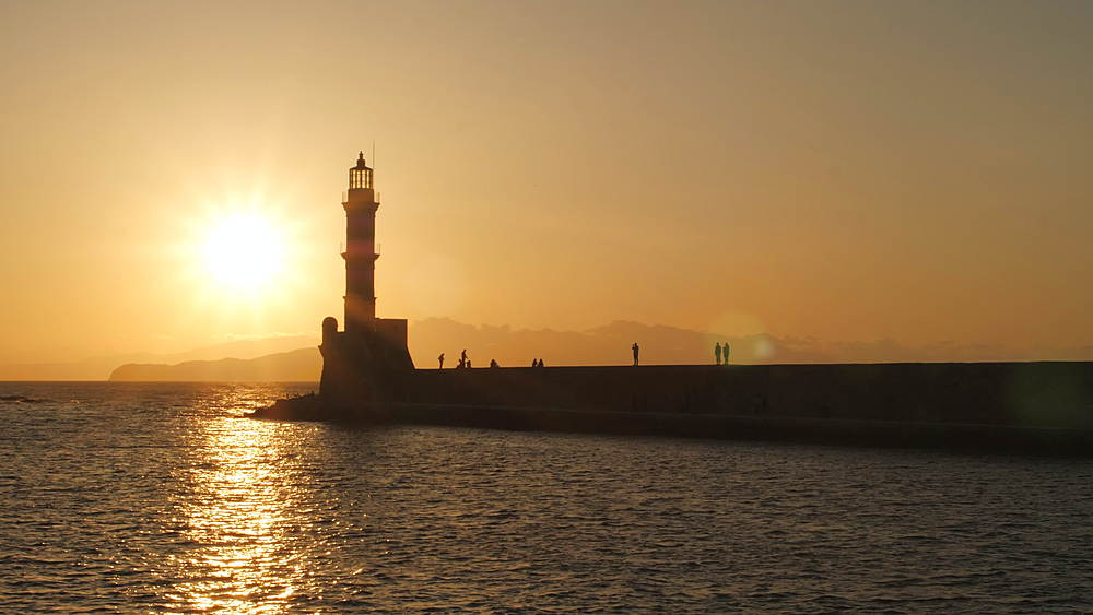 Sunset over The Venetian era harbour and lighthouse at the Mediterranean port of Chania, Crete, Greek Islands, Greece, Europe