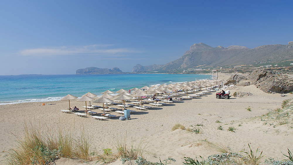 Umbrellas on the beach and emerald seas at Falassarna beach in Western Crete, Greek Islands, Greece, Europe