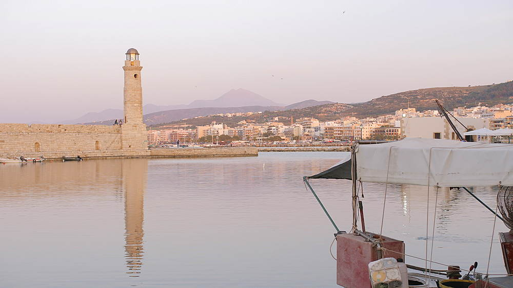 Sunset over Lighthouse at old Venetian harbour, Rethymno, Crete, Greek Islands, Greece, Europe