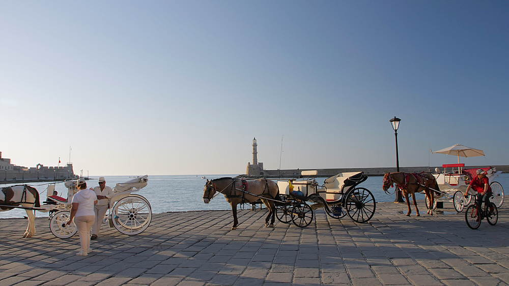 Horse Carriage, The Venetian era harbour and lighthouse at the Mediterranean port of Chania, Crete, Greek Islands, Greece, Europe
