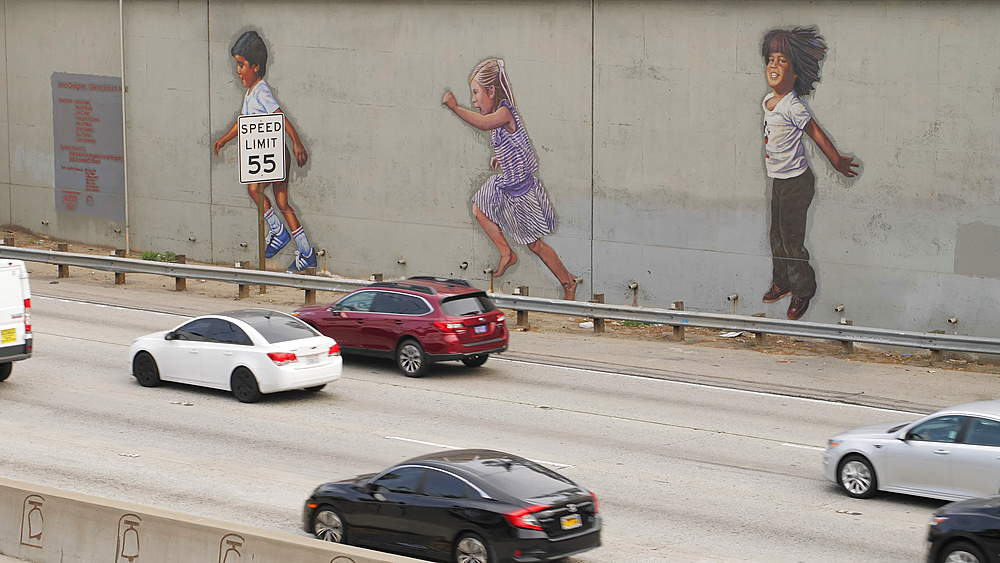 Traffic and paintings of children on Highway 101 in Downtown near City Hall, Los Angeles, LA, California, USA, North America