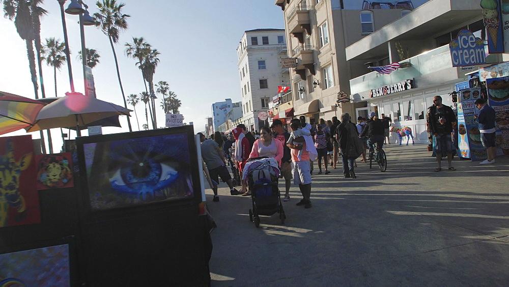 Tracking shot of pedestrians walking at Venice Beach on Ocean Avenue, Sant Monica, Los Angeles, LA, California, USA, North America - 1276-987