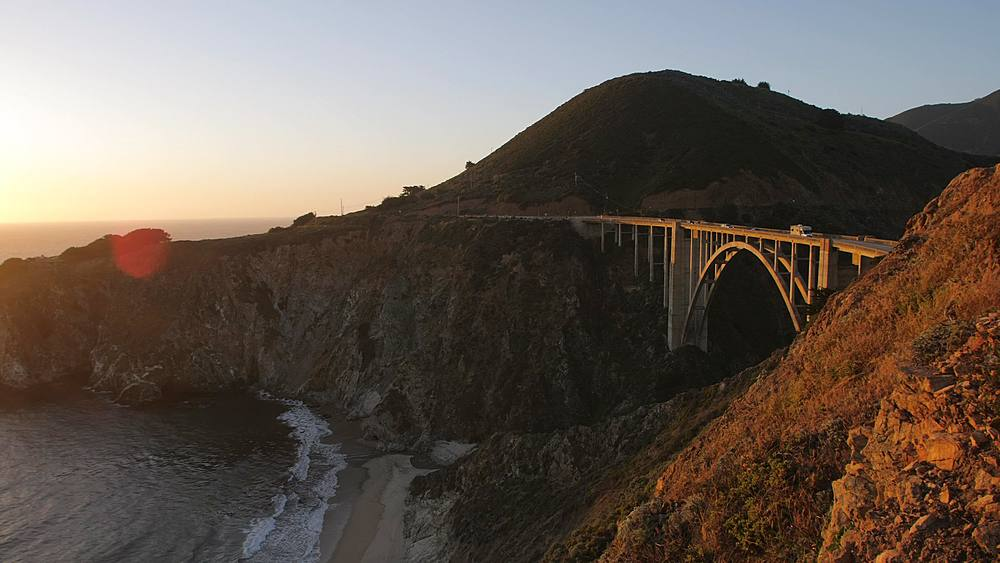 Panning shot of sunset from Cabrillo Highway 1 over Bixby Creek Bridge at Big Sur, California, United States of America, North America
