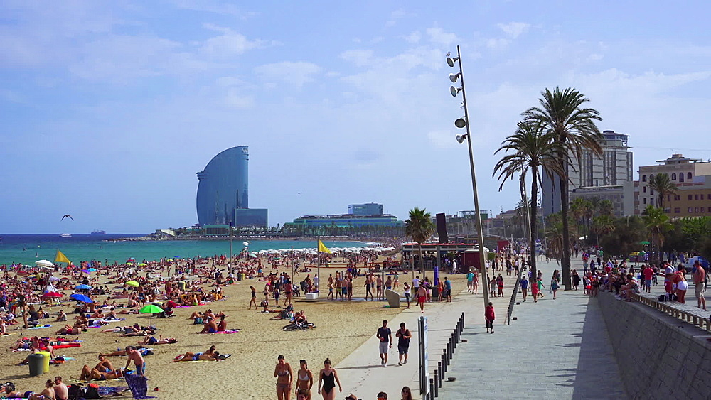 Bathers on a crowded sandy beach with background view of W sail shaped hotel, Barcelona Beach, Catalonia, Spain, Europe - 1278-106
