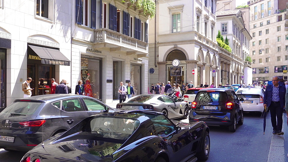 Milan, Italy Via Monte Napoleone shopping street with luxury cars. People outside Milano fashion district Dolce & Gabbana shop. - 1278-112