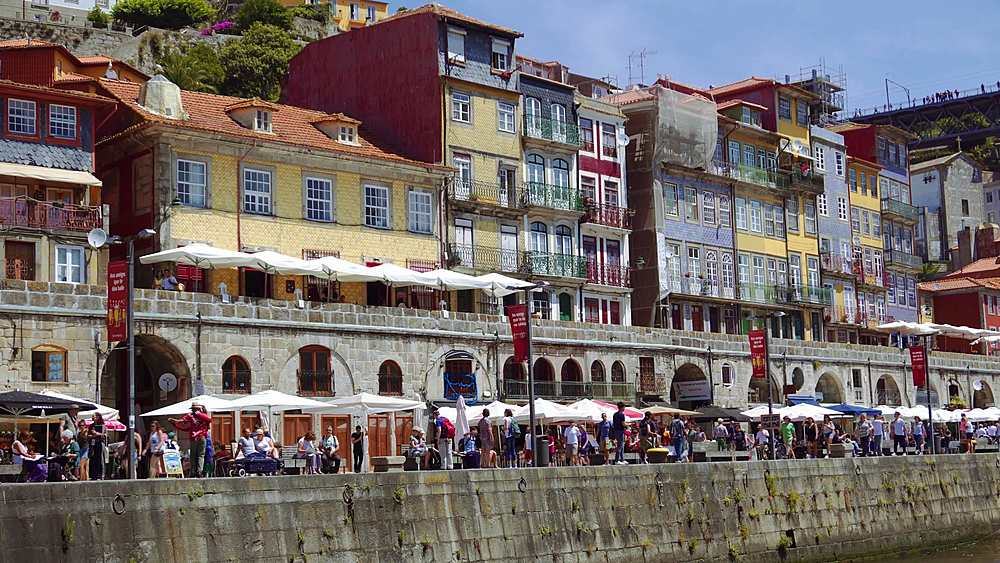 Porto, Portugal Ribeira traditional waterfront houses. Duro river sea view of colorful buildings with crowd on Duro river bank.