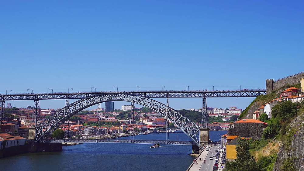 Porto, Portugal day view of Dom Luis I bridge over Douro river. Background view of Vila Nova de Gaia with traditional buildings.