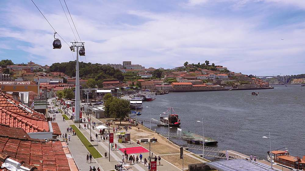 Porto, Portugal Vila Nova de Gaia waterfront panoramic view with traditional buildings and moving cable cars.