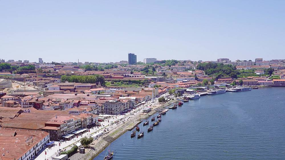 Porto, Portugal Vila Nova de Gaia waterfront panoramic view. Moored Douro river Porto wine boats before buildings and shops.