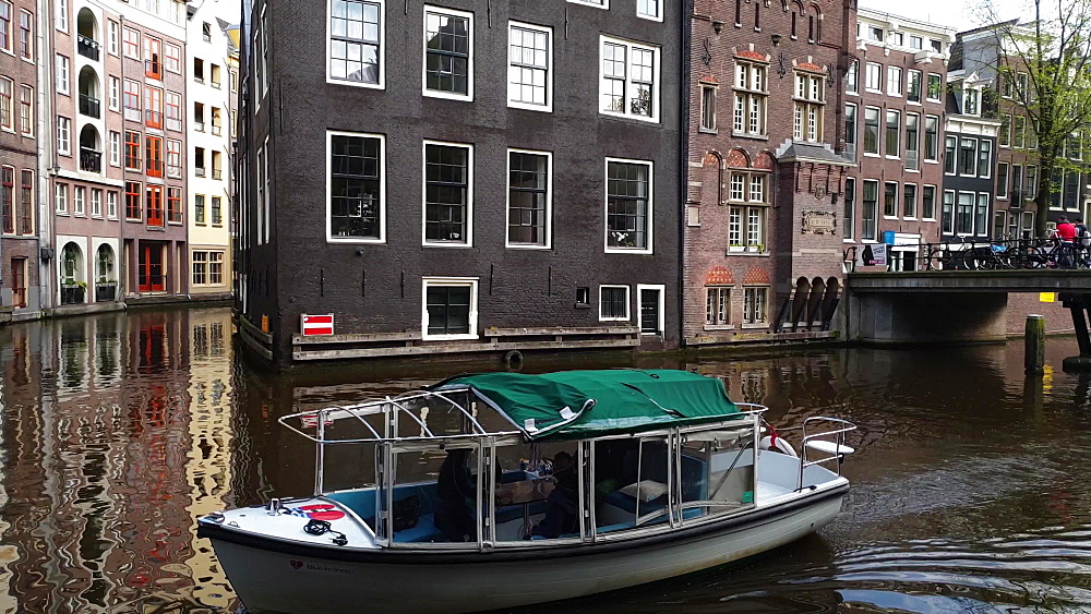 A boat on a canal in the red light district in Amsterdam, North Holland, The Netherlands, Europe