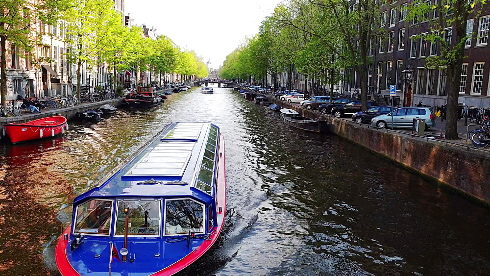 Canal in the center of Amsterdam with a boat passing by, Amsterdam, North Holland, The Netherlands, Europe - 1300-370