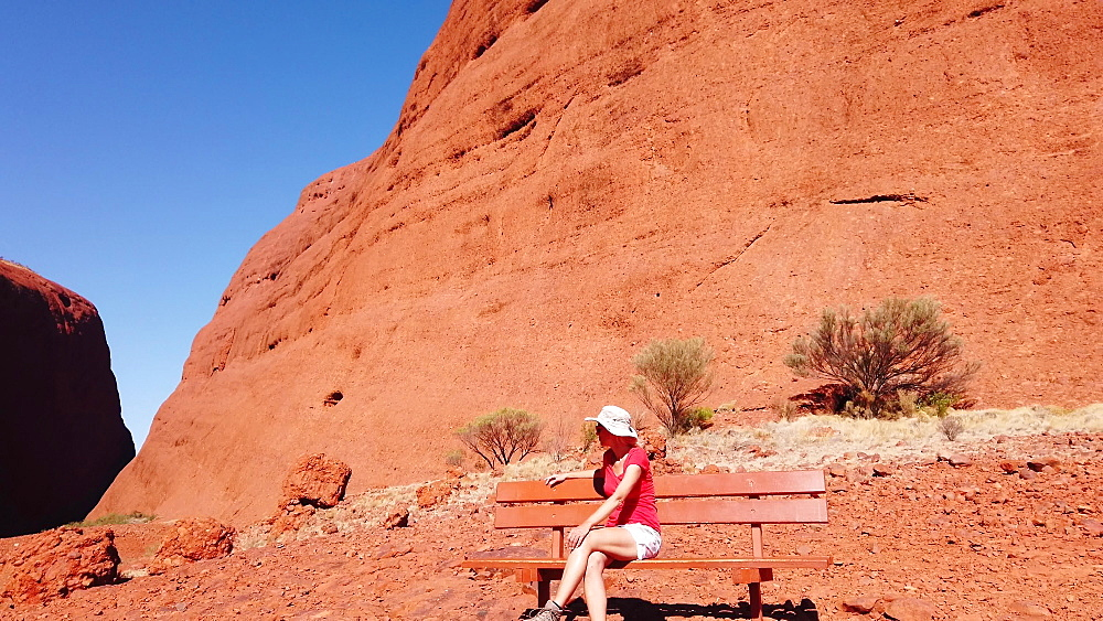 Tourist woman relaxing on bench at entrance to the gorge along Walpa Gorge Walk in Uluru-Kata Tjuta National Park, UNESCO World Heritage Site, Red Centre, Outback, Northern Territory, Australia, Pacific