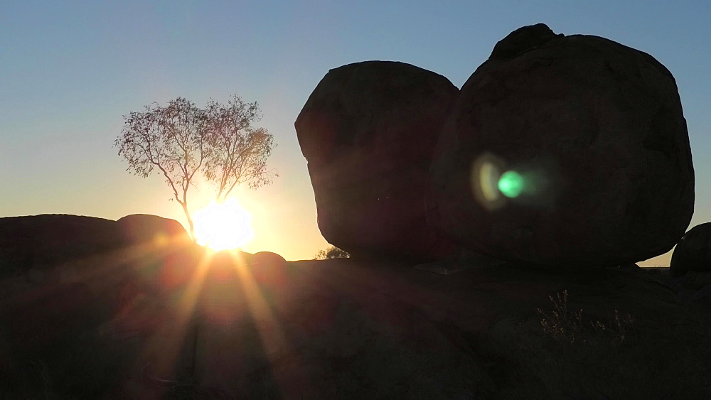 Sunbeams at dawn behind Devils Marbles, Eggs of mythical Rainbow Serpent, Karlu Karlu Devils Marbles Conservation Reserve, a most famous natural wonder in Northern Territory, Australia, Pacific - 1314-175