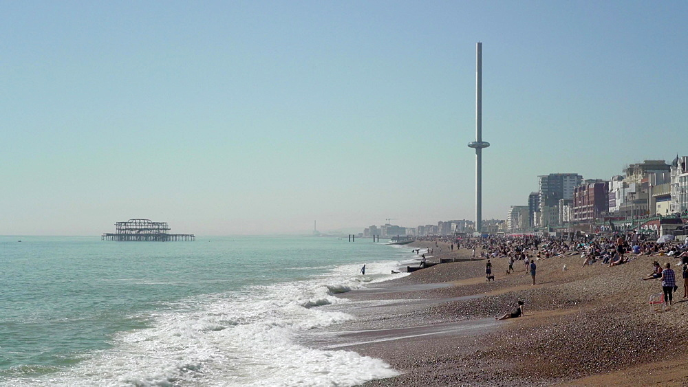Brighton Beach full of tourirts in sun with i360 and paragliders, Brighton, East Sussex, England, United Kingdom, Europe
