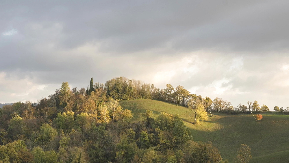 Time lapse of sunset in autumn above the hills with moving clouds, Emilia Romagna, Italy, Europe