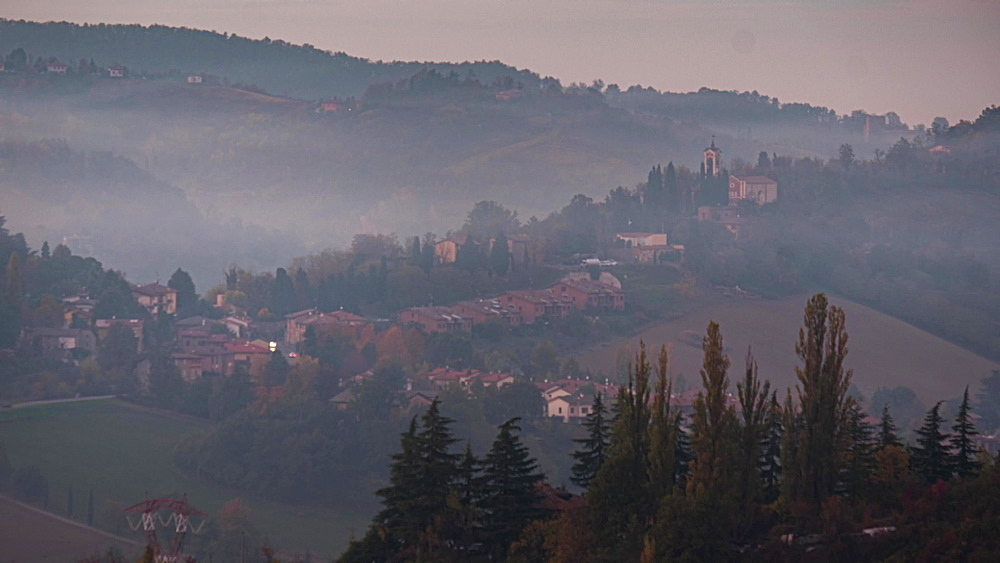 Blue hour time lapse of a small town in a valley and a smoke cloud moving, Emilia Romagna, Italy, Europe