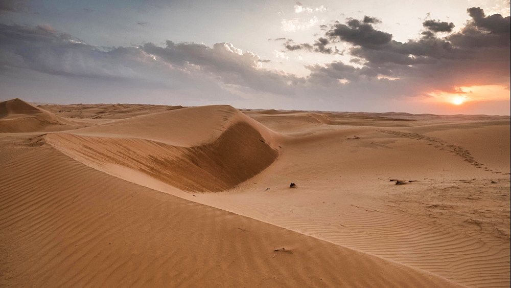 Time lapse of sunset in the Wahiba Desert with a cloudy sky, Oman, Middle East