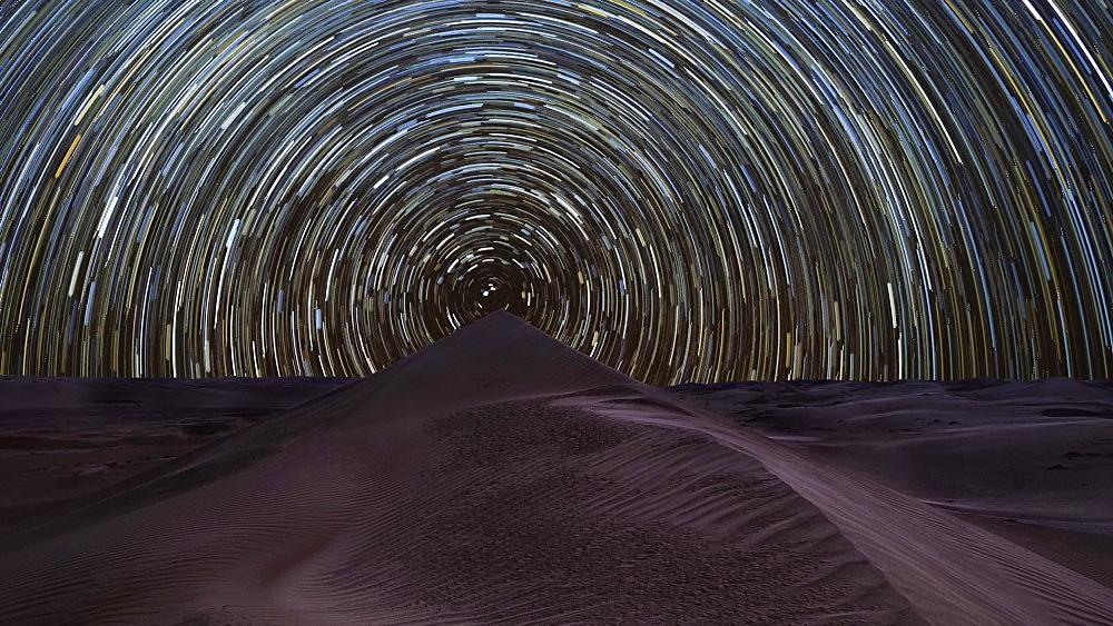 Night time lapse of a circumpolar concentric star trail in the Rub Al Khali desert, Oman, Middle East