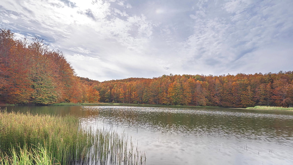 Time lapse of an autumnal landscape with lake, foliage and moving clouds, Emilia Romagna, Italy, Europe