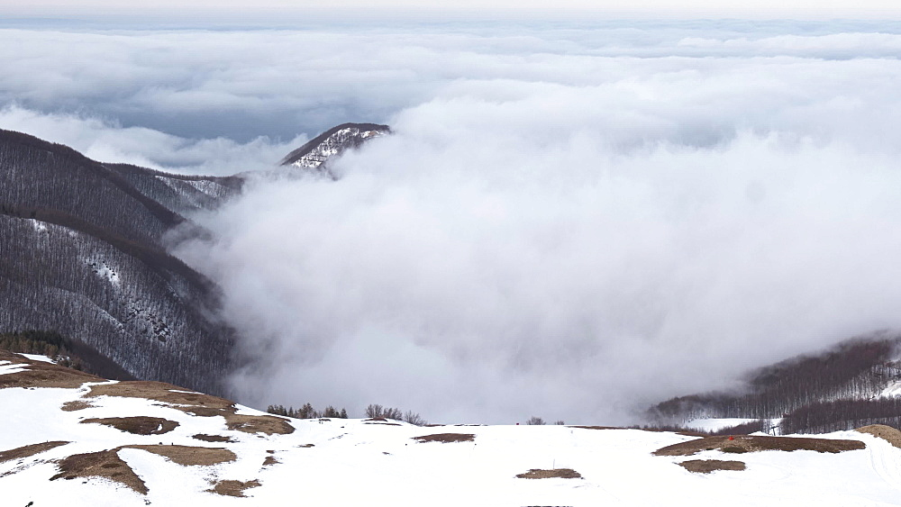 Time lapse of low clouds and fog from a snowy mountain point of view, Emilia Romagna, Italy, Europe