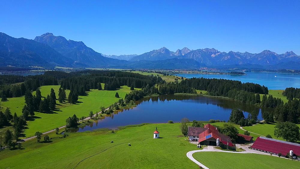 Aerial view of a chapel and a farm on Lake Hergratsried and Lake Forggensee near F?ssen, Allgaeu, Swabia, Bavaria, Germany - 396-8386