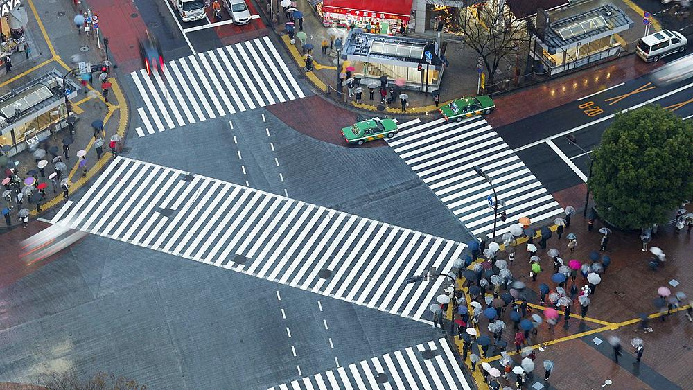Asia, Japan, Tokyo, Shibuya, Shibuya Crossing - crowds of people crossing the famous crosswalks at the centre of Shibuyas fashionable shopping and entertainment district