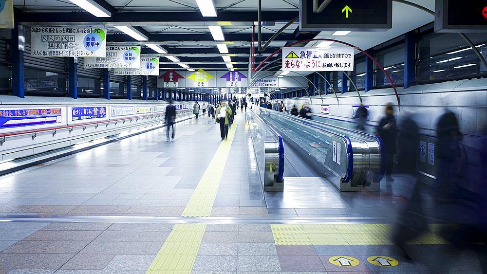 T/L Commuters on a moving walkway in  Shibuya Station at rush hour, Shibuya, Tokyo, Honshu, Japan