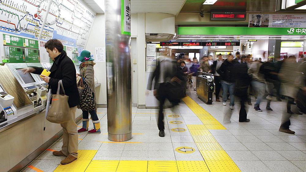 T/L Commuters buying subway tickets from ticket machines at Shinjuku Station , Honshu, Tokyo