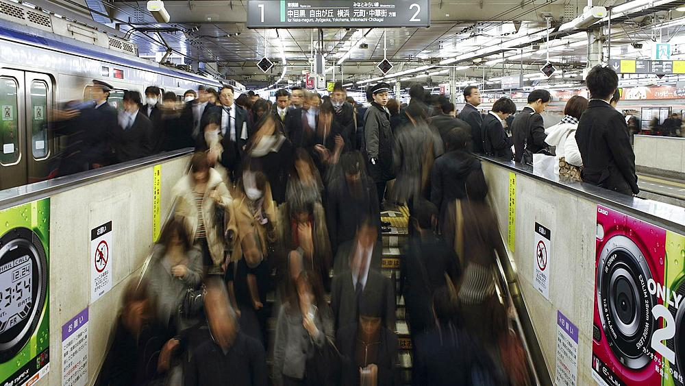 T/L Commuters tmoving on an escalator in Shibuya Station at rush hour, Shibuya, Tokyo, Honshu, Japan