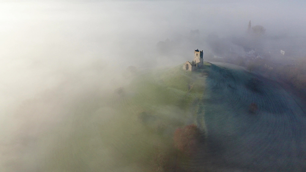 Aerial of the ruins of St. Michaels Church on Burrow Mump surrounded by mist, Burrowbridge, Somerset, England, United Kingdom, Europe