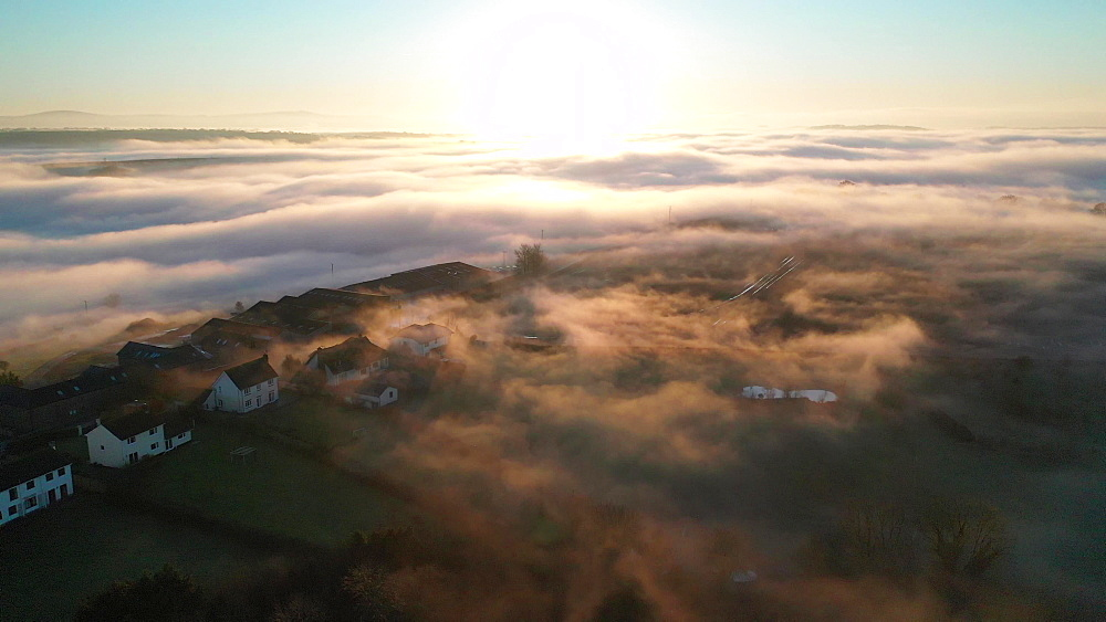 Aerial of fog over a village at sunset, Coldridge, Devon, England, United Kingdom, Europe