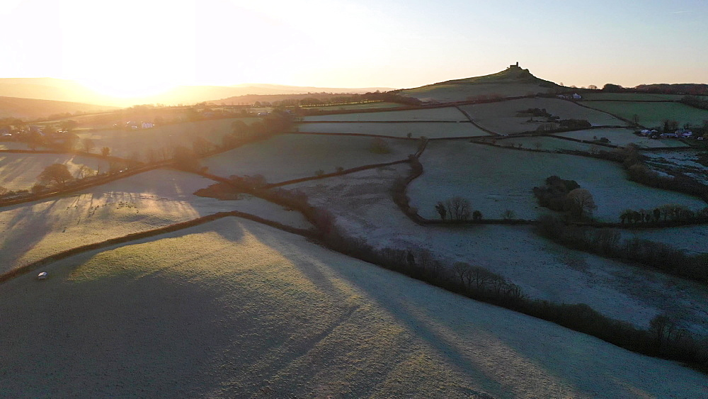 Aerial clip of frosty rolling countryside at sunrise, Brentor, Devon, England