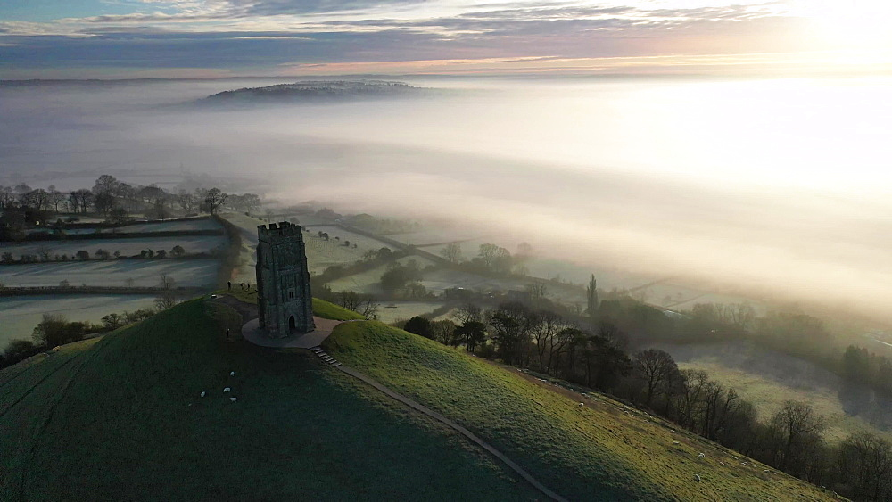 Aerial of Glastonbury Tor in morning winter light, Glastonbury, Somerset, England, United Kingdom, Europe